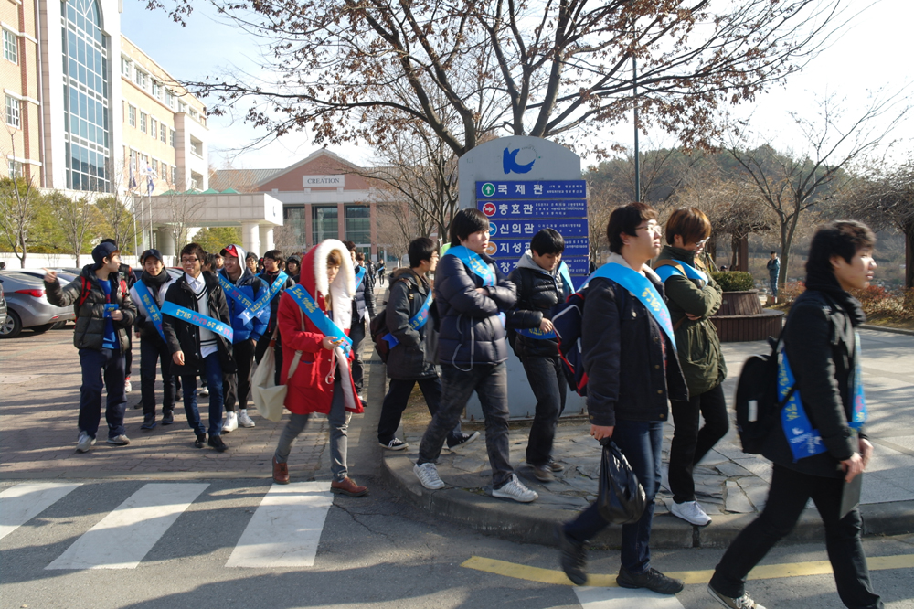 국제대학교 학생들이 에너지절약에 대한 홍보어깨띠를 두르고 행진 중이다.