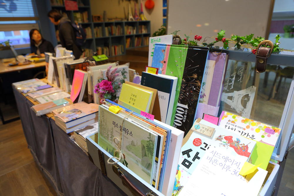 '과천 타샤의 책방'은 주로 그림책을 다루는 책방이다. 자연을 벗하며 어린이들을 위한 그림책을 만든 타샤 튜터처럼 한평생 책과 함께하고 싶은 마음에 '타샤의 책방'으로 이름 지었다.
